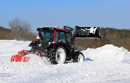 traktor pfluegt schnee auf einem yard