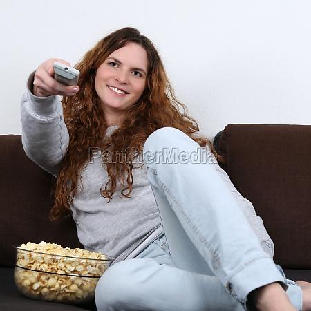 junge frau schaut fernsehen und isst