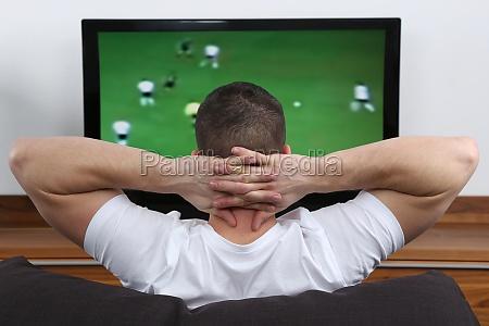 junger mann schaut fussball im fernsehen