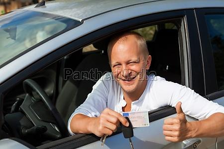 junger erwachsener mann im neuen auto