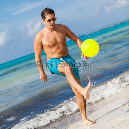 laughing young man playing soccer ball