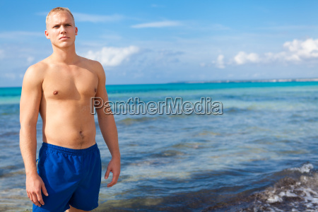 athletic young man in swimming trunks