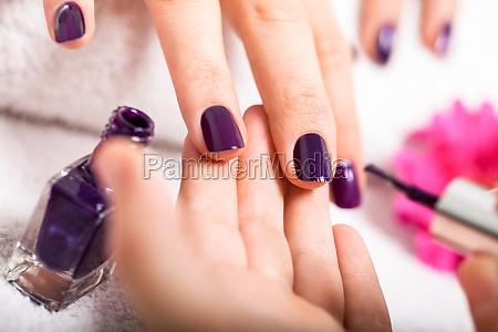 frau bekommt ihre naegel in lila
