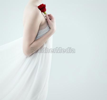 frau haelt rote rose an die