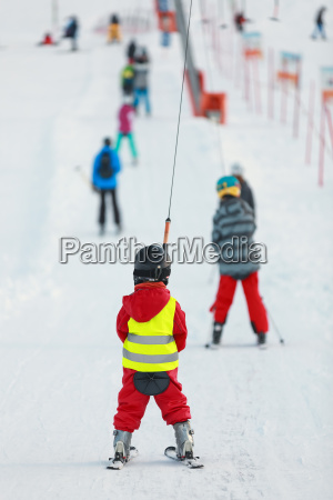 kind mit rotem skianzug am schlepplift