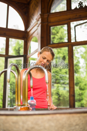 young woman fillig a plastic bottle