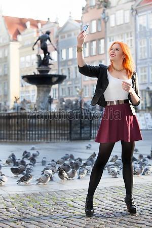 traveler red hair girl taking photo
