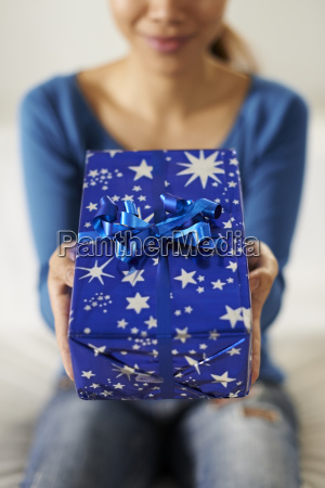 asian girl holding gift box to