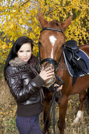 equestrian with her horse in autumnal