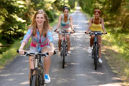 drei weibliche freunde reiten fahrraeder im