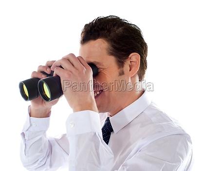 male executive looking through binoculars