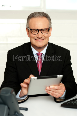 senior executive sitting with tablet pc