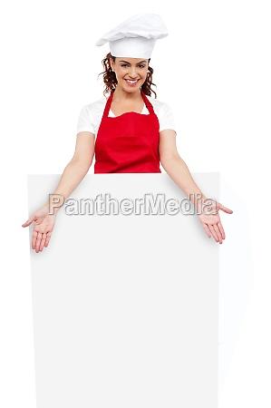 female chef posing behind blank white