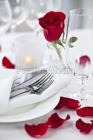 romantische dinner kulisse mit rosenblaettern