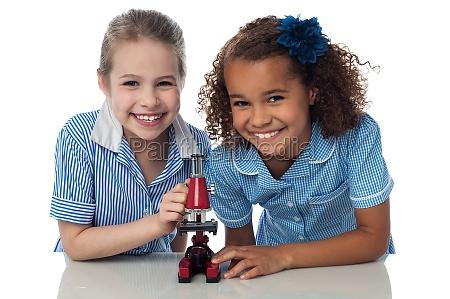 joyous junge schulmaedchen mit mikroskop