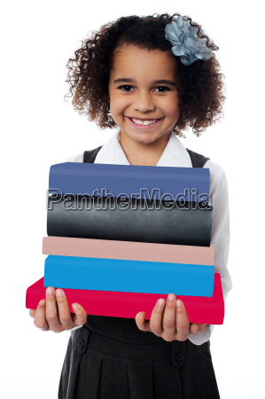 cute school girl carrying stack of