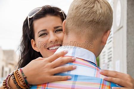 junge attraktive frau umarmt gefuehlvoll ihren