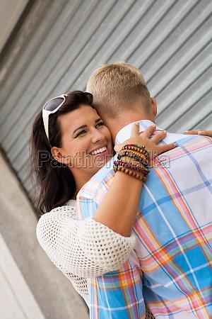 blonder junger mann umarmt seine freundin