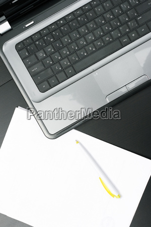 laptop and blank paper sheet on