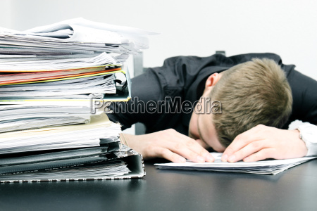 tired office worker and a pile