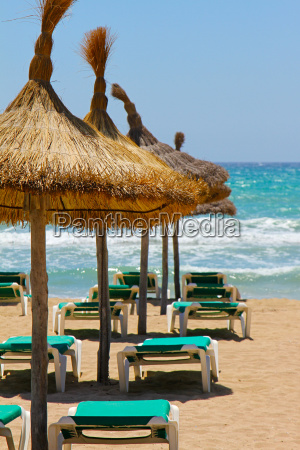 loungers and straw umbrellas on the