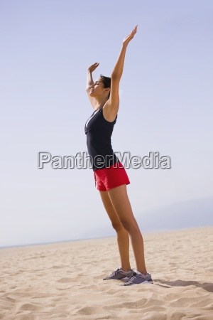 young athletic female with arms raised