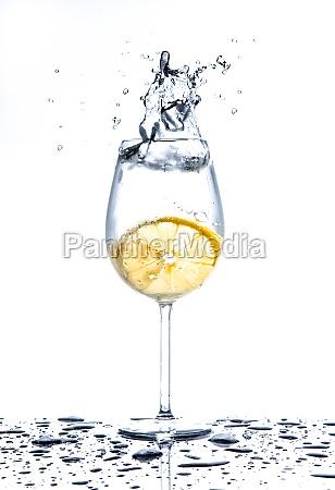zitrone spritzen in glas wasser auf