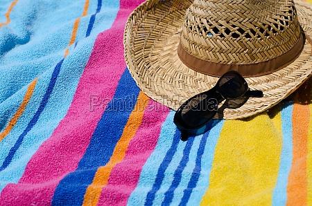 urlaubskonzept mit strandtuch sonnenhut und sonnenbrille