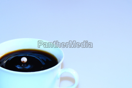 kaffee mit huepfenden milchtropfen