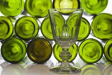 rotweinglas vor weinflaschen