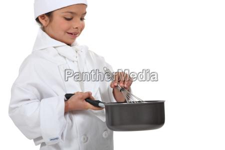 young chef mixing a sauce