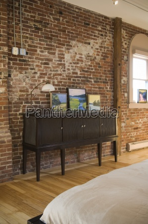 cabinet in bedroom against brick wall