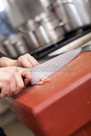 koch schneidet frisches rotes fleisch in
