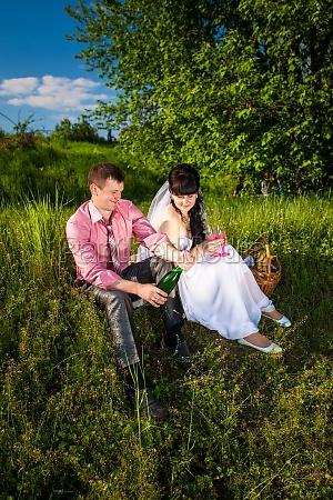 braeutigam oeffnet champagner auf picknick im