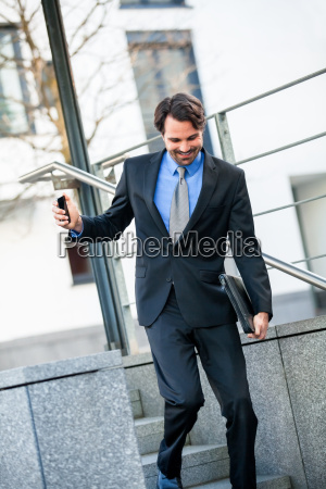 froehlicher erfolgreicher geschaeftsmann mit dunklem anzug