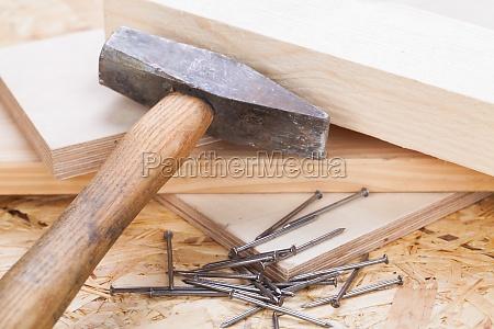 hammer mit naegeln auf einem holzbrett
