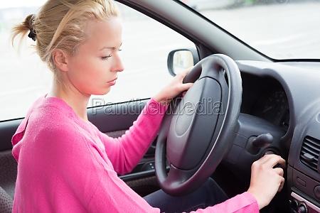 weiblicher autofahrer der den motor anfaengt