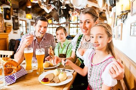 bavarian family in german restaurant eating