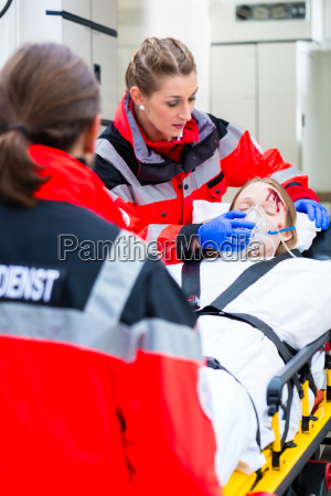 ambulance helping injured woman on stretcher