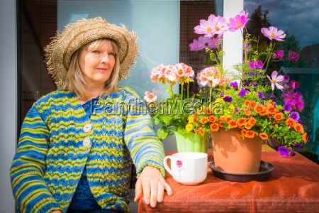 woman sitting with flowers on balcony