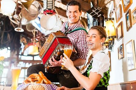 musiker im bayerischen restaurant spielt akkordeon