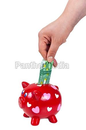 handeinfuegung 100 euro banknote in sparschwein