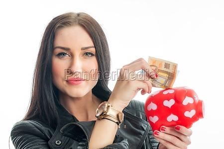 woman puts money into a piggy