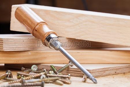 nahaufnahme eines kreuz schraubendrehers mit schrauben