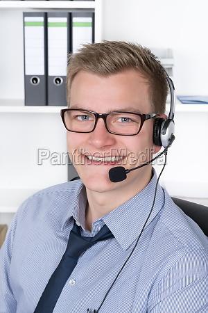junger laechelnder mann mit headset im