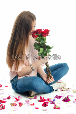 girl sits amid rose petals