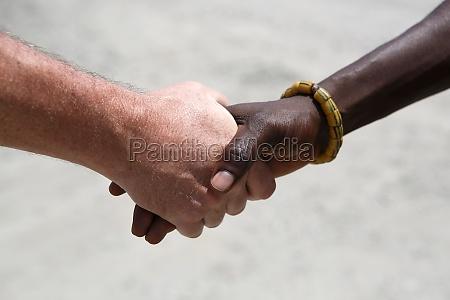 hand begruessung zwischen einer kaukasischen und