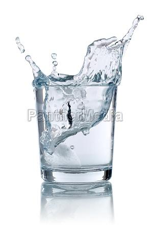 eiswuerfel faellt in ein glas mit