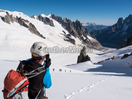 mountaineer taking picture with a camera