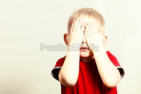glueckliche kindheit blonder junge mit kinderbedeckungsgesicht